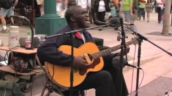 Han sätter sig ner mitt på gatan och börjar sjunga - se hur människorna runt om ansluter sig